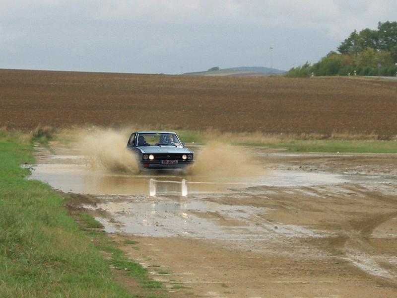 Wasserlache - der lachende Fahrer fährt durch die Pfütze