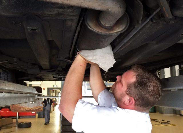Schrauben unterm Auto in perfekten Arbeitsklamotten